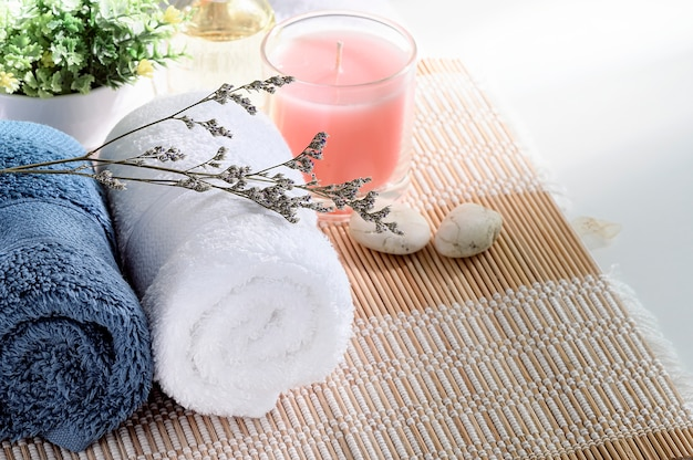 Roll up of clean towels on white table with candle and houseplant, copy space.