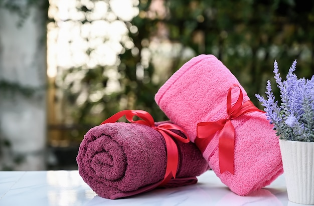 Roll up of colorful towels on white table with copy space on blurred garden background.