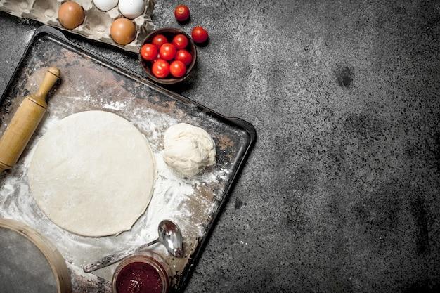 ピザの材料で生地を丸めます。素朴な背景に。