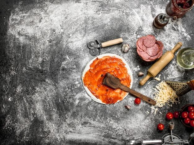 トマトソースとさまざまな材料で生地を丸めます。素朴な背景に。