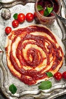 토마토 소스와 다양한 재료로 반죽을 굴립니다.
