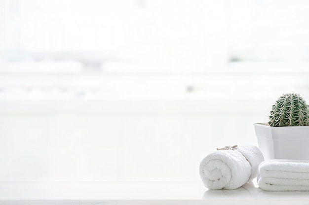 ぼやけたリビングルームの背景にコピースペースと白いテーブルの上の白いタオルのロールアップ。製品展示モンタージュ用。