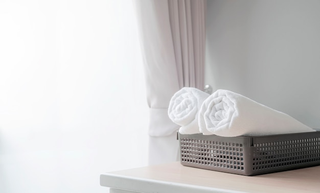 Roll of white clean bath towels in basket on wooden table in hotel room, copy space.