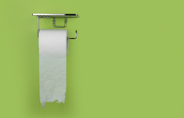 Roll of white toilet paper on a background of green wall copy space. shortage of toilet paper.