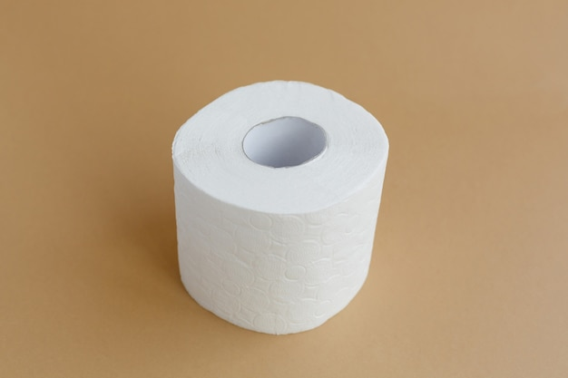 Roll of white toilet paper on a brown background