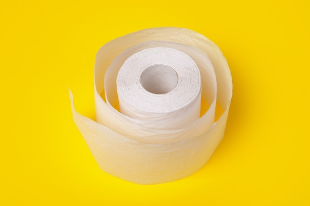Roll of white toilet paper over yellow background