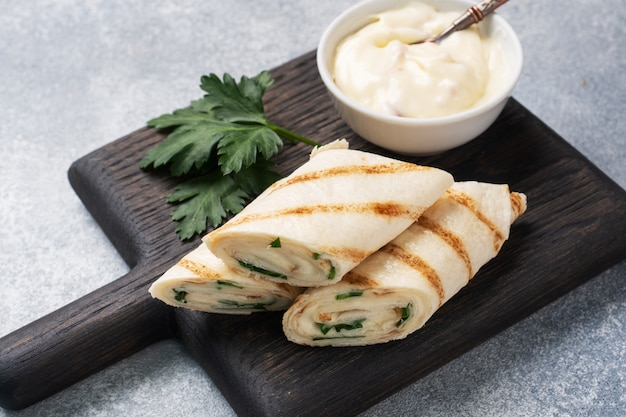 Roll with cheese and herbs. grilled pita bread with filling. cucumber radish salad. concept of a healthy breakfast.