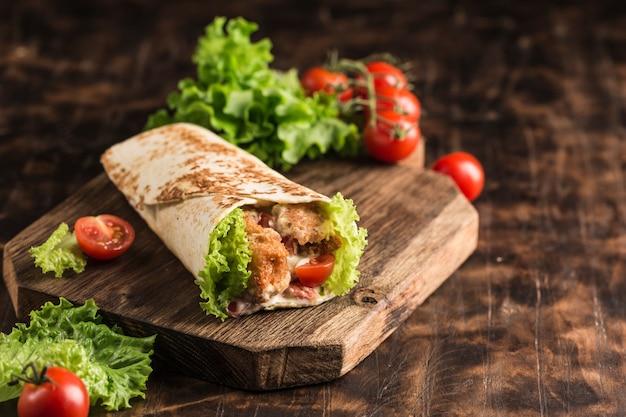 Ролл с курицей и свежими помидорами черри и листьями салата на деревянной доске