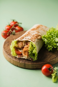 Roll with chicken and fresh cherry tomatoes and lettuce on a wooden board
