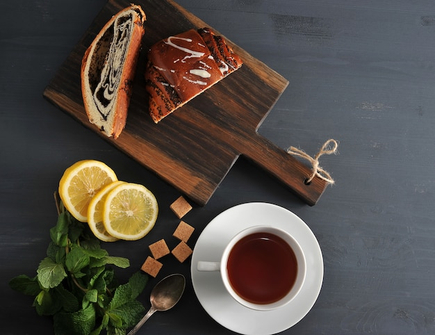 Roll with poppy seeds, tea, lemon and mint on wooden surface