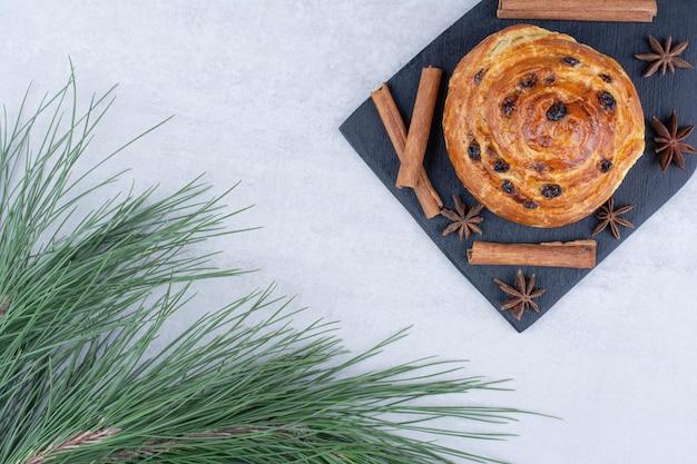 Rotolo con uvetta su tavola nera con cannella e chiodi di garofano. foto di alta qualità