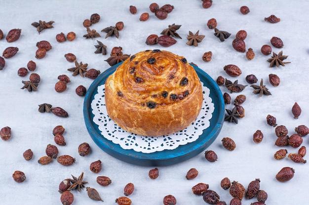 Rotolo con uvetta su piatto blu con cinorrodi e chiodi di garofano. foto di alta qualità