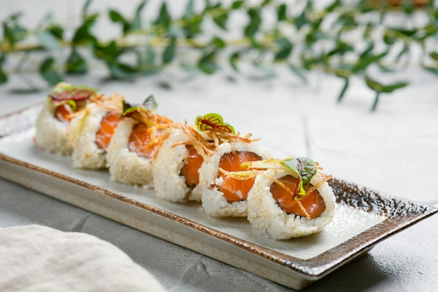 Roll with salmon and microgreen on ceramic plate closeup with copy space