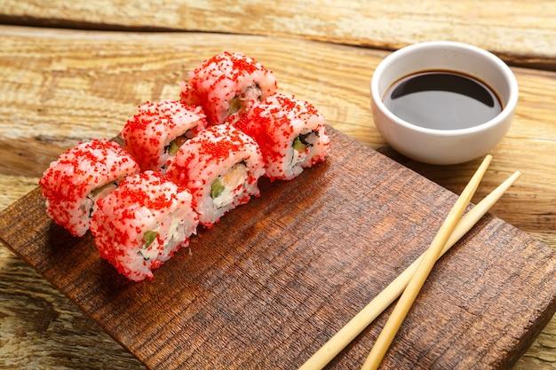 Ролл с креветками, огурцом и красной икрой тобико, палочками на доске и соевым соусом в соуснице на деревянном фоне. горизонтальное фото