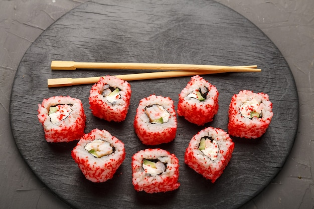 Roll with shrimp and tobiko caviar and sticks on a black round board on a gray background. copy space horizontal photo