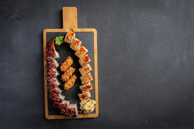 Ролл с копченым угрем, сыром и рукколой. установить суши-ролл. традиционная японская кухня. изолированные на черном.