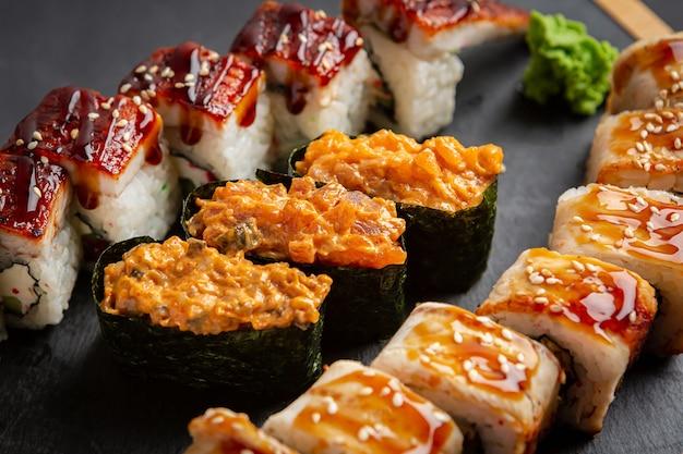 Ролл с копченым угрем, сыром и рукколой. установить суши-ролл. традиционная японская кухня.