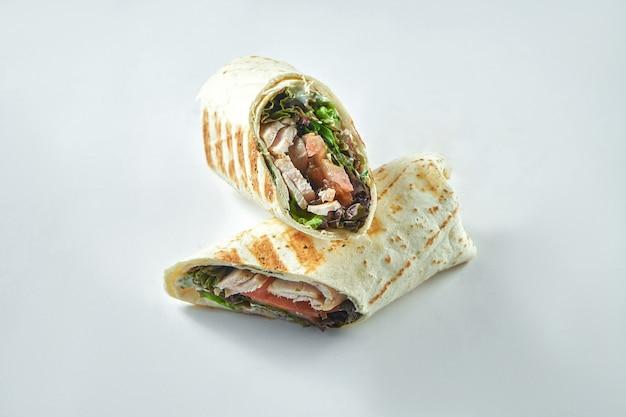 七面鳥、野菜、サラダの葉と一緒に巻いてください。白い皿にラヴァッシュで白身の肉とダイエットシャワルマ