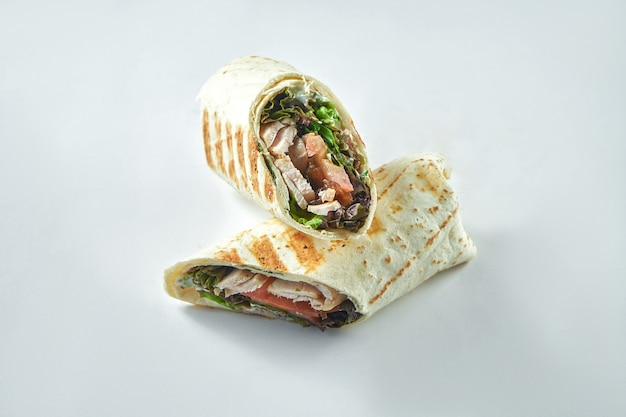 Roll with turkey, vegetables and salad leaves. diet shawarma with white meat in lavash on a white plate