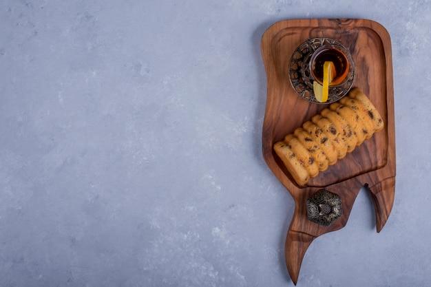 木製の大皿、トップビューでアールグレイティーを添えてロールケーキ