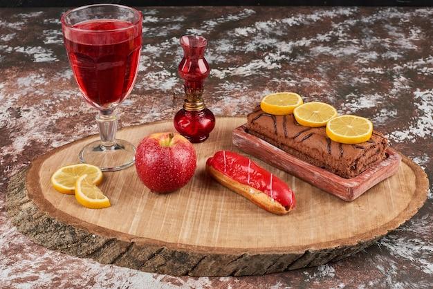 Роллкейк с бокалом вина на деревянной доске.