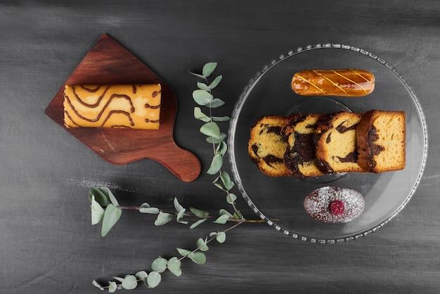 Роллкейк с эклерами и кусочками пирога.