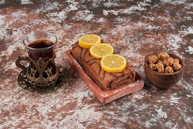 Rollcake con un bicchiere di tè su una tavola di legno.