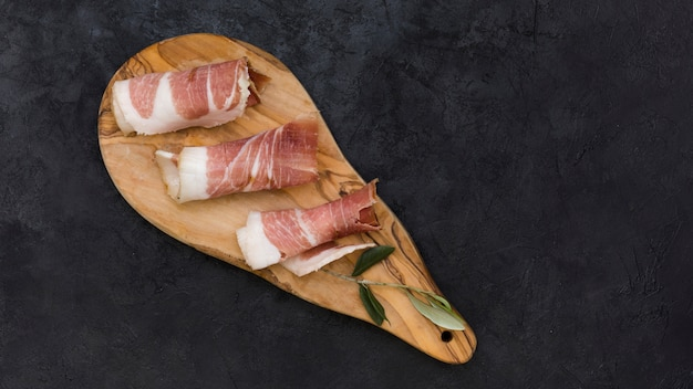Rolled bacon and olive leaf on wooden serving board against black textured background