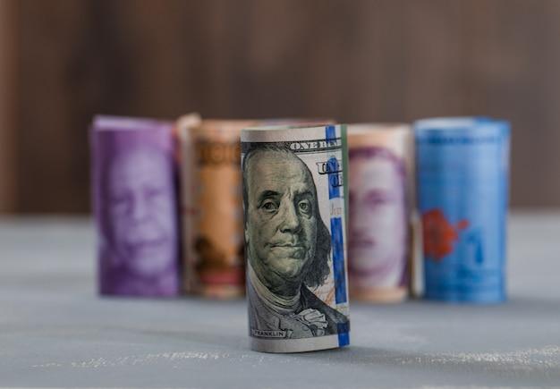 Свернутые банкноты на гипсе и деревянном столе.
