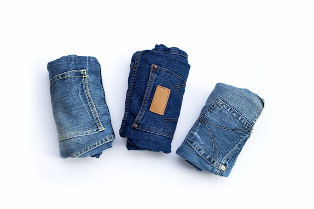 Rolled blue jeans on white background