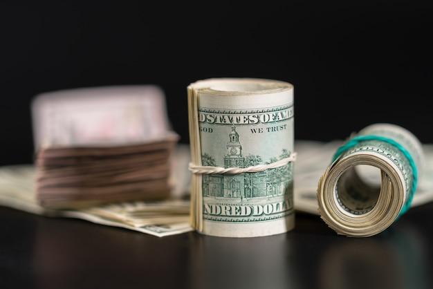 Свернутая пачка американских банкнот, перевязанная резинкой на черном столе