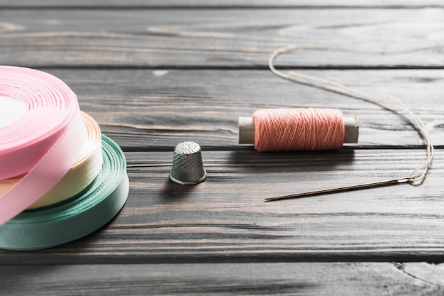 Rolled colorful ribbons and sewing item on wooden table