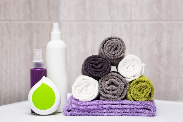 Rolled cotton fluffy towels of different colors bottles of shampoos and balms brushing comb hair care and washing