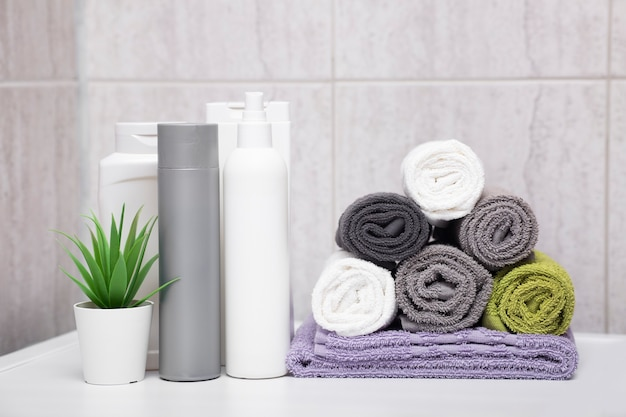 Rolled cotton fluffy towels of different colors, bottles of shampoos and balms, a plant in a pot in the bathroom