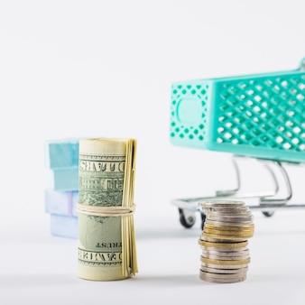 흰색 테이블에 압 연된 달러와 동전 스택