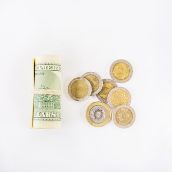 Rolled dollars and coins on table
