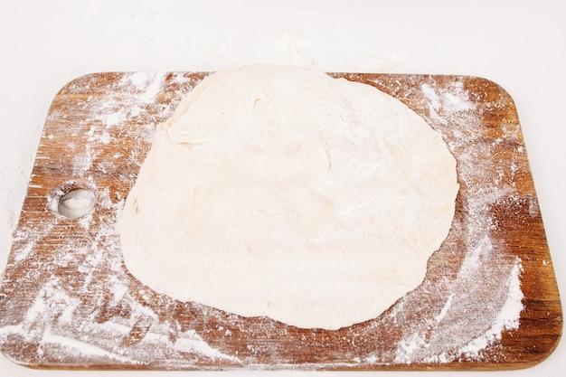 Раскатанное тесто на деревянной разделочной доске
