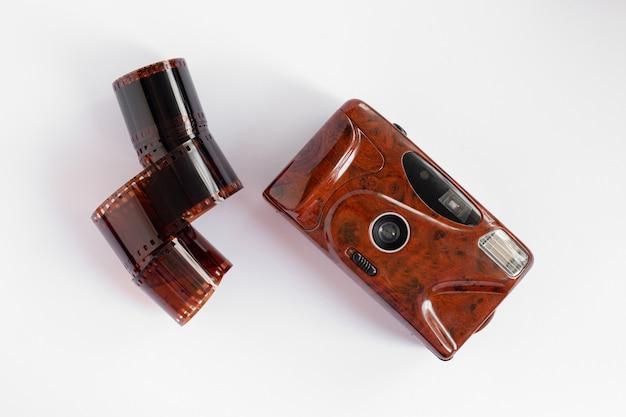 白い孤立した表面に赤い色のロールフィルムとフィルムレトロカメラ。アナログ写真のコンセプト