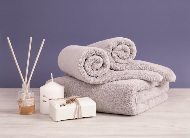 Rolled and folded gray terry towels with soap and candles against lilac wall