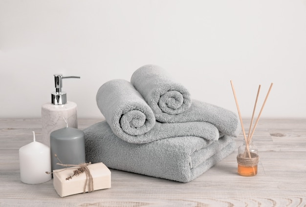 Rolled and folded gray terry towels with soap and candles against white wall
