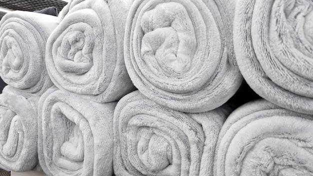 Свернутые серые одеяла в магазине продаются. мягкие пушистые бежевые пледы продаются на полке магазина.