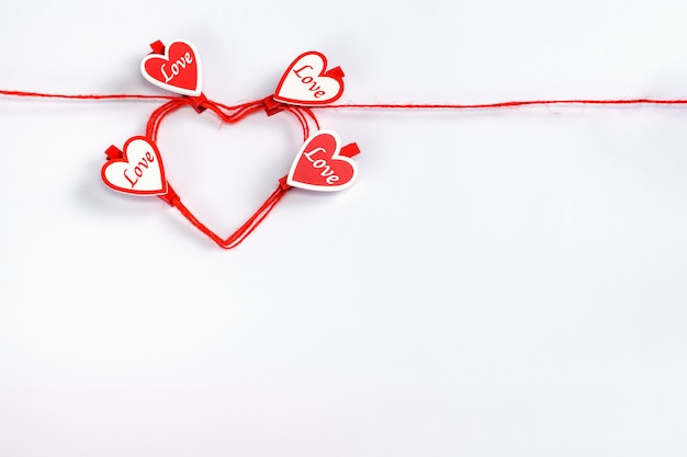 Rolled in heart shape red rope with clothespins in shape of hearts on a white for valentines day