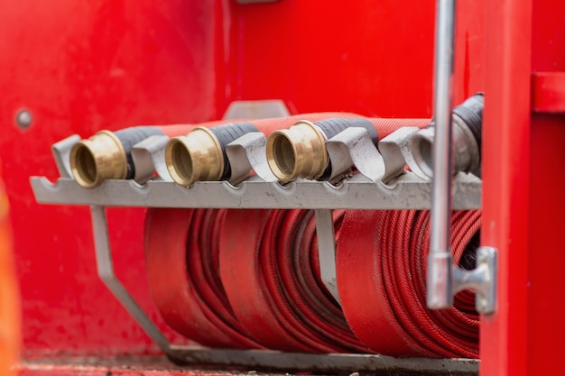 Rolled into a roll red fire hose, fire equipment extinguishers ready to use
