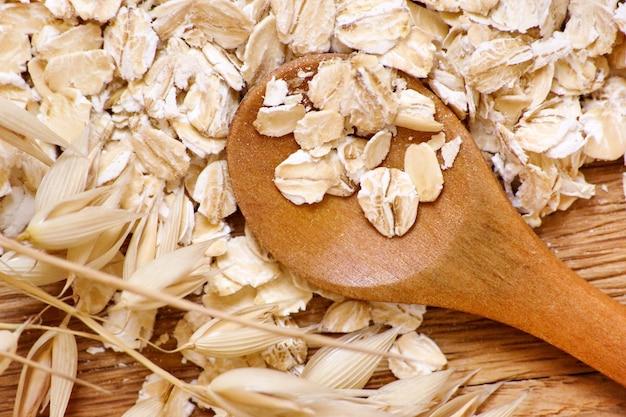 ロールドオーツとオーツ麦の穂を木製のテーブルに、クローズアップ