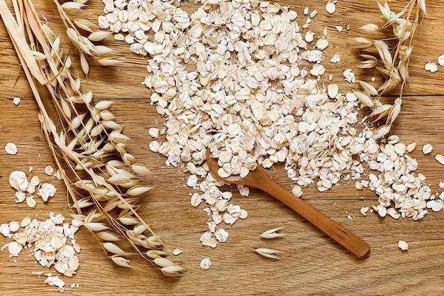 木製のテーブルの上に巻かれたオーツ麦と穀物のオーツ麦の穂