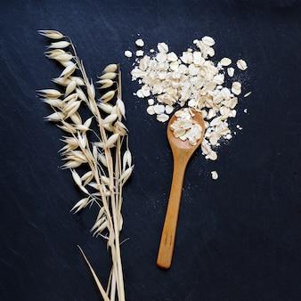 黒の背景にロールドオーツと穀物のオーツ麦の耳