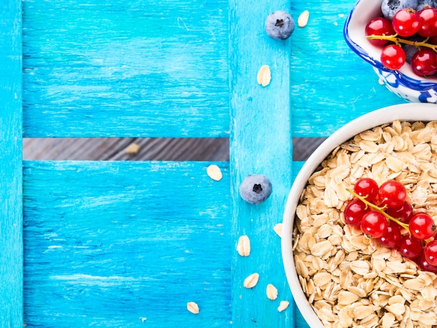 Rolled oats and berries on blue textured