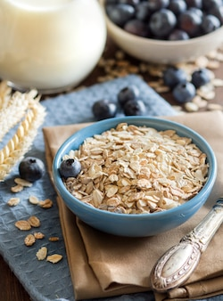 Rolled oats in a bowl with berries and milk on a napkin on a wooden table close up