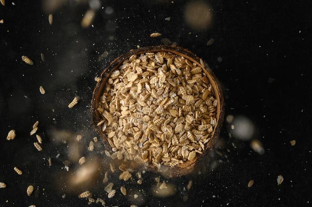 濃い灰色の表面にココナッツ ボウルに入れたオート麦の穀物