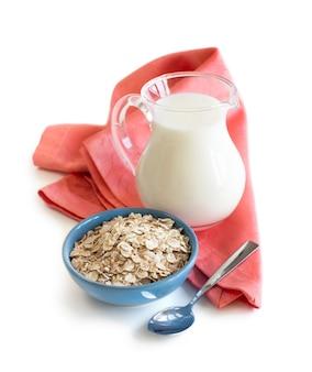 Овсяные хлопья в миске и молоко на деревянном столе